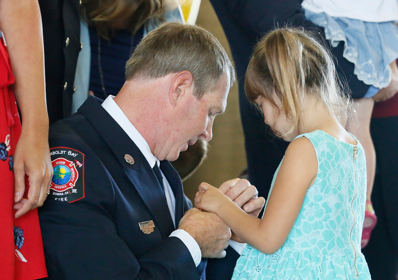 Shaun Walker — The Times-Standard  Newly-promoted Humboldt Bay Fire Captain David Terry get his badge pinned on him by his daughter Anika, 4, during a ceremony at fire headquarters in Eureka on Friday. The event also included the following promotions: new Chief Sean Robertson, new Firefighter Nicholas Lyvers, Tim Citro promoted to battalion chief, Kris Kalman promoted to captain, Adam Bumgardner promoted to engineer, Michael Tyson promoted to engineer, and also John Owens completion of the volunteer academy.