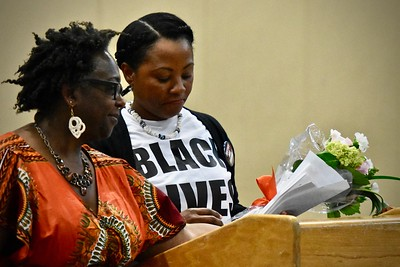 Michelle Charmaine Lawson, mother of slain Humboldt State University student David Josiah Lawson, is handed flowers by local NAACP leader Lorna Bryant moments before Bryant announced the David Josiah Lawson Memorial Scholarship.