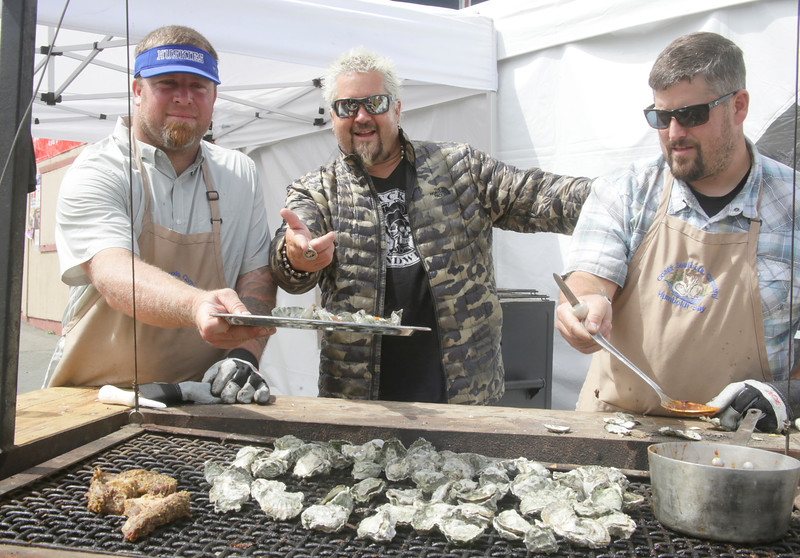Shaun Walker — The Times-Standard  Food Network star and Ferndale native Guy Fieri, center, visits with Gary Klinetob, left, and Ryan Kleiner of Coast Seafoods and Fortuna Huskies Football and their Humboldt Bay Kumamoto oysters at the fair's Surf and Turf BBQ Contest on Thursday.