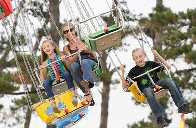 Shaun Walker — The Times-Standard  Lilly Nochera of Garberville, 9, left, mom Tammy, and brother Milo, 11, ride The Wave Swinger at the Humboldt County Fair in Ferndale on Thursday. Horse racing resumes at the fair at 3:07 p.m. today, and the fair is hosting their Date Night Challenge.