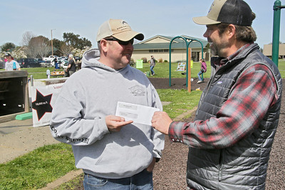 """Shaun Walker — The Times-Standard  Chris Edwards of Redding gets a $1,000 check from Dave Feral of Humboldt Steelhead Days for winning the fishing contest with a 27.5"""" hatchery steelhead."""