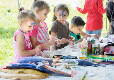 Shaun Walker — The Times-Standard  Madisyn [CQ] Castillo, 4, sister KayLee, 5, cousin Yaretzi Castillo, 5, and cousin Joshua Castillo, 9, paint wooden fish at the Humboldt Steelhead Days carnival in McKinleyville on Saturday.