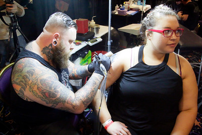 Shaun Walker — The Times-Standard  Cody Hennings of Dallas, Texas, tattoos Erika Givens of Eureka.