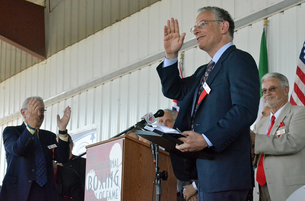 . KYLE MENNIG � ONEIDA DAILY DISPATCH Class of 2017 inductee Steve Farhood waves to the crowd after his speech at the induction ceremony as Barry Tompkins, left, and Don Ackermann applaud during the International Boxing Hall of Fame\'s 28th annual Induction Weekend in Canastota on Sunday, June 11, 2017.