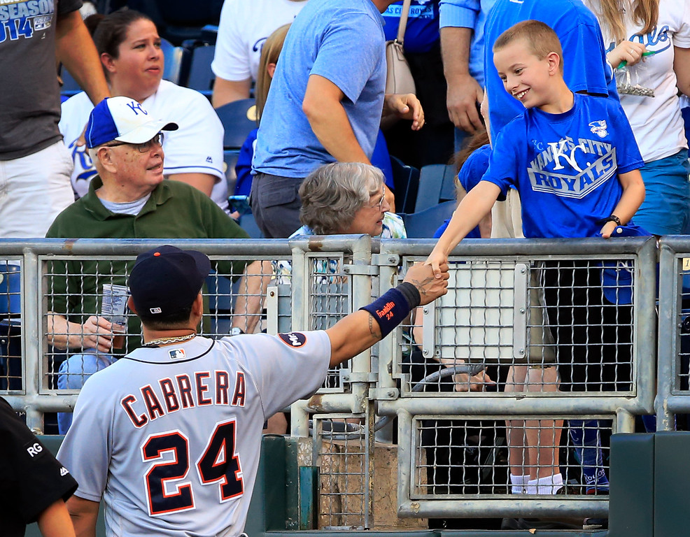 . Detroit Tigers first baseman Miguel Cabrera (24) shakes hands with a young Kansas City Royals fan after chasing a foul ball into the stands during the third inning of a baseball game at Kauffman Stadium in Kansas City, Mo., Tuesday, May 30, 2017. (AP Photo/Orlin Wagner)
