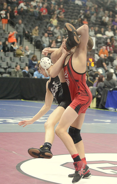 . Loveland\'s Cody Thompson picks up the leg of Pueblo South\'s Mac Martinez in their 106-pound first-round match of the 4A state wrestling tournament at the Pepsi Center in Denver on Thursday. Thompson advanced with an 8-6 decision.