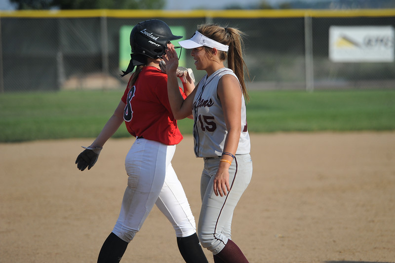 Bailey Cocke, left, high-fives Addison Spears after Loveland's softball game against Berthoud on Thursday, Aug. 23, 2018 at Centennial Park in Loveland, Colorado. (Sean Star/Loveland Reporter-Herald)