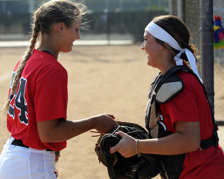 Loveland pitcher Laurin Krings, left, hands catcher Elana Gerhard her gear during the Indians' 10-0 win Thursday, Aug. 23, 2018 at Centennial Park. (Sean Star/Loveland Reporter-Herald)