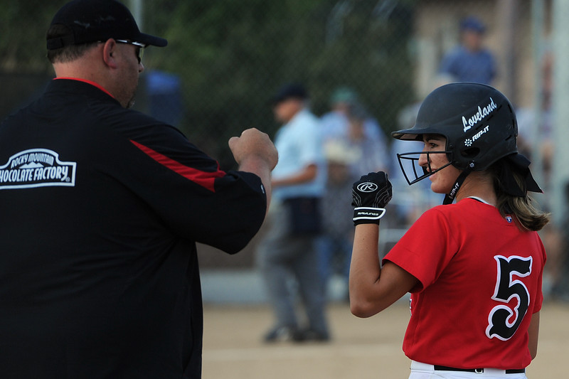 First base coach A.J. Clark fist bumps Jordan Irwin during Loveland's softball game against Berthoud on Thursday, Aug. 23, 2018 at Centennial Park in Loveland, Colorado. (Sean Star/Loveland Reporter-Herald)