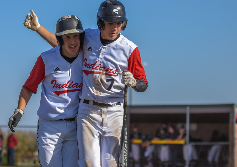 Loveland's Jackson Bakovich, left, is hugged by teammate Zach Harstad after scoring a run against Monarch on Thursday April 26, 2018 at Swift Field. (Cris Tiller / Loveland Reporter-Herald)