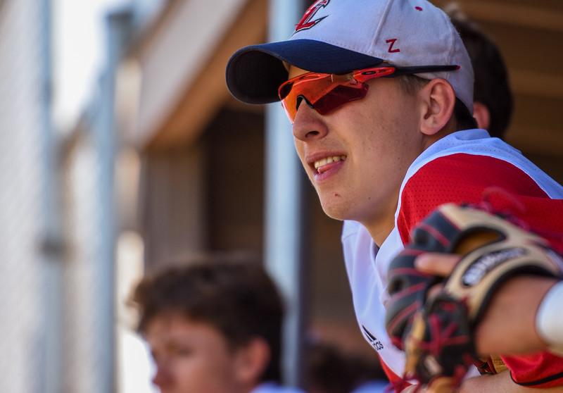 Loveland's Jackson Bakovich looks on from the dugout against Monarch on Thursday April 26, 2018 at Swift Field. (Cris Tiller / Loveland Reporter-Herald)