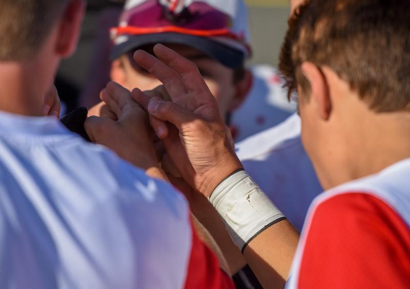 Loveland baseball players huddle up after a loss against Monarch on Thursday April 26, 2018 at Swift Field. (Cris Tiller / Loveland Reporter-Herald)