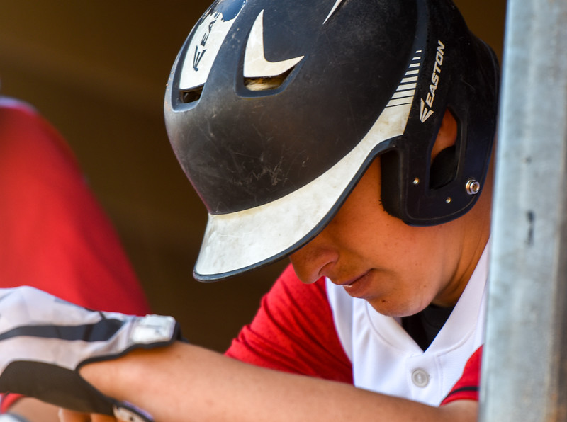 Loveland's Jackson Bakovich looks down in thought between innings against Monarch on Thursday April 26, 2018 at Swift Field. (Cris Tiller / Loveland Reporter-Herald)