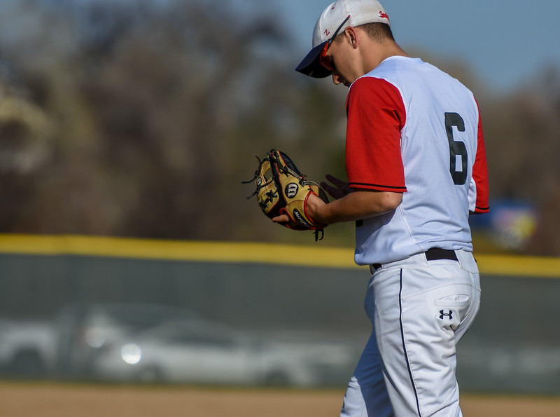 Loveland's Jackson Bakovich inspects his glove against Monarch on Thursday April 26, 2018 at Swift Field. (Cris Tiller / Loveland Reporter-Herald)