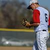 Loveland's Jackson Bakovich inspects his glove against Monarch on Thursday April 26, 2018 at Swift Field. (Cris Tiller / Loveland Reporter-Herald)