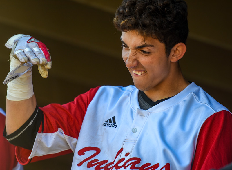 Loveland's Keegan Villarreal describes the movement of a pitch in the dugout against Monarch on Thursday April 26, 2018 at Swift Field. (Cris Tiller / Loveland Reporter-Herald)