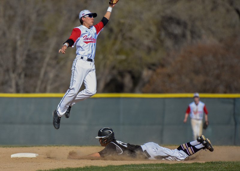Loveland second baseman Jaxon Cabrera goes up for a catch as a Monarch player slides into the base Thursday April 26, 2018 at Swift Field. (Cris Tiller / Loveland Reporter-Herald)