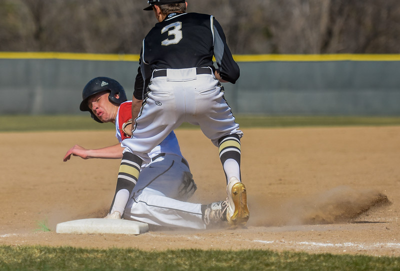 Loveland's Heron Lenze is tagged out at third base against Monarch on Thursday April 26, 2018 at Swift Field. (Cris Tiller / Loveland Reporter-Herald)