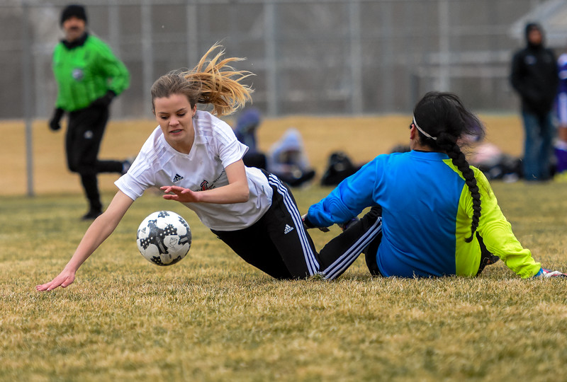 Loveland's Ava Hannaford, left, goes to ground after a sliding tackle from Mountain View goalkeepr Beatriz Lopez on Thursday March 29, 2018 at MVHS. (Cris Tiller / Loveland Reporter-Herald)