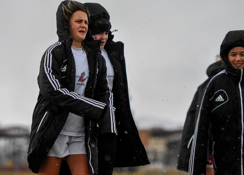 Loveland players try to stay warm between halves as the snow falls against Mountain View on Thursday March 29, 2018 at MVHS. (Cris Tiller / Loveland Reporter-Herald)