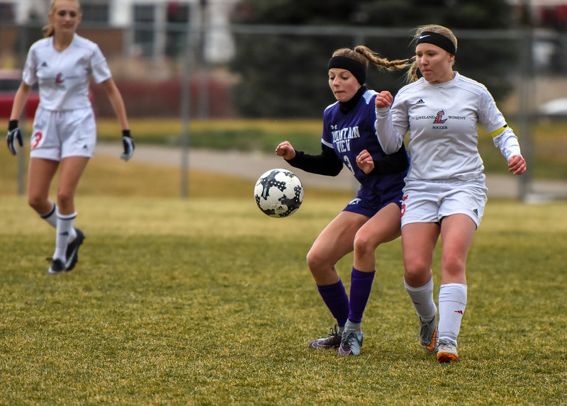 Mountain View's Jacey Paoli, left, and Loveland's Tessa Madsen battle for the ball Thursday March 29, 2018 at MVHS. (Cris Tiller / Loveland Reporter-Herald)