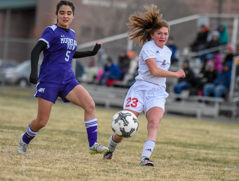 Loveland's Carissa Morrison (23) makes a cross in front of Mountain View's Alyssa Perez on Thursday March 29, 2018 at MVHS. (Cris Tiller / Loveland Reporter-Herald)