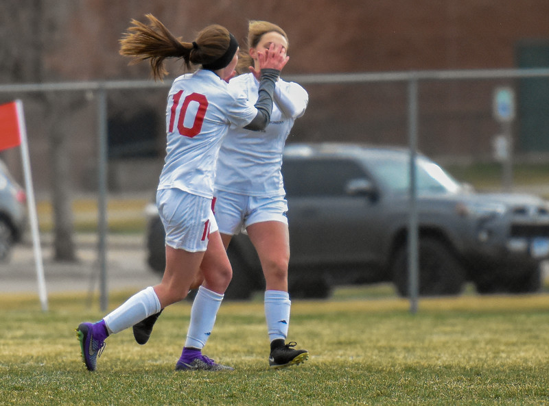 Loveland's Maraia Rubin (10) high fives a teammate after scoring her hat-trick goal against Mountain View on Thursday March 29, 2018 at MVHS. (Cris Tiller / Loveland Reporter-Herald)