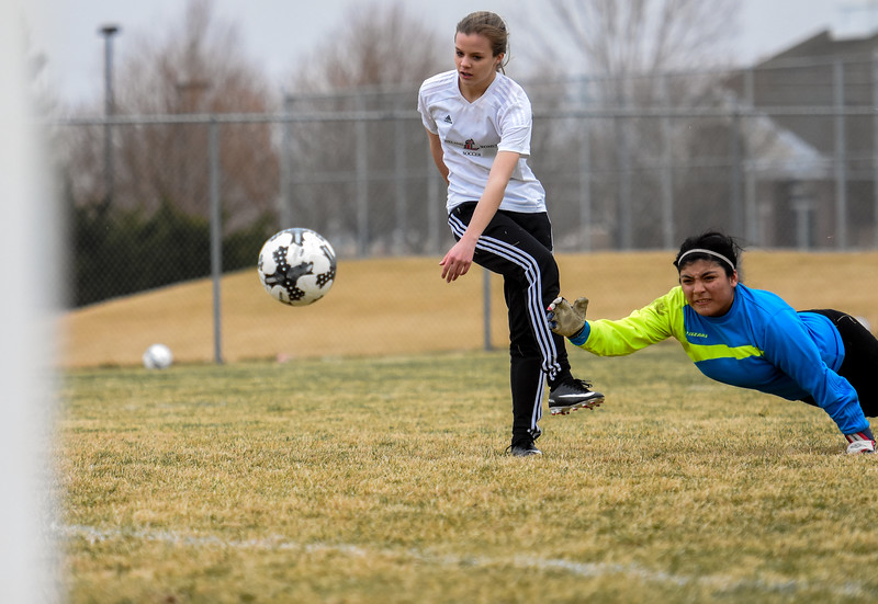 Loveland's Ava Hannaford, left, eyes her goal as Mountain View keepr Beatriz Lopez makes a diving save attempt Thursday March 29, 2018 at MVHS. (Cris Tiller / Loveland Reporter-Herald)