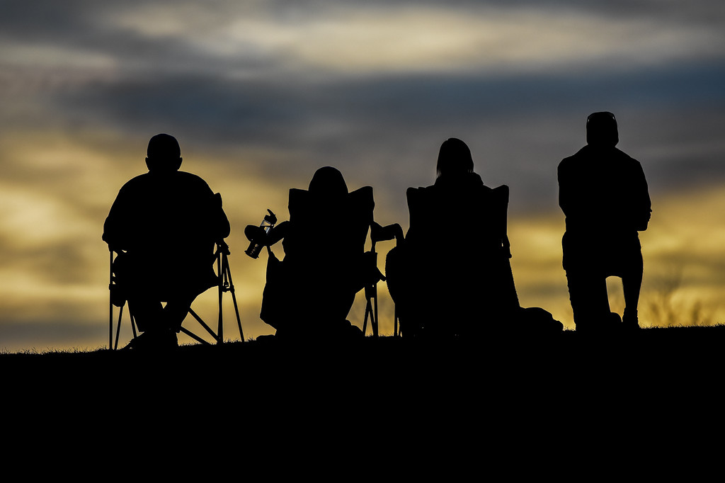 . Spectators watch from atop a hill as the sun wanes on Thursday March 8, 2018 at North Lake Park. (Cris Tiller / Loveland Reporter-Herald)