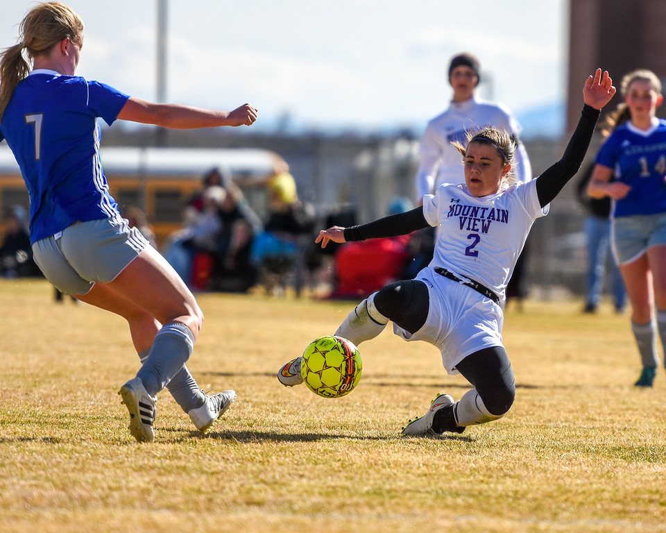 Mountain View's Kaley Barker (2) goes in for a tackle on Resurrection Christian's Olivia Swan (7) on Tuesday March 20, 2018 at MVHS. (Cris Tiller / Loveland Reporter-Herald)