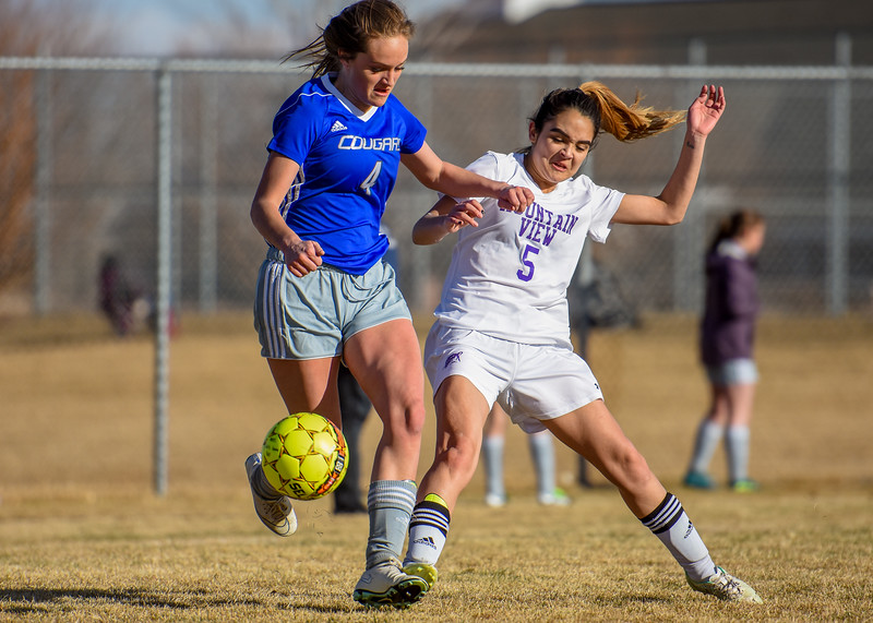 Mountain View defender Alyssa Perez (5) makes a tackle against Resurrection Christian's Jenni Pronozuk (4) on Tuesday March 20, 2018 at MVHS. (Cris Tiller / Loveland Reporter-Herald)