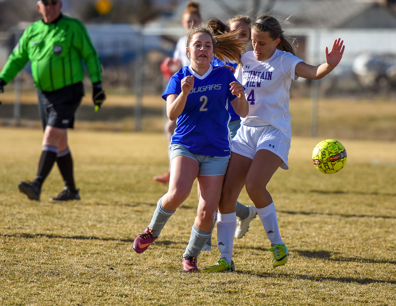Resurrection Christian's Sadie Barger (2) and Mountain View's Kennedy Neustel (4) battle for a loose ball on Tuesday March 20, 2018 at MVHS. (Cris Tiller / Loveland Reporter-Herald)