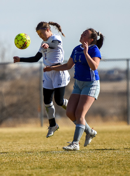 Mountain View's Kaley Barker (2) rises for a header in front of Resurrection Christian's Kensey Bishop on Tuesday March 20, 2018 at MVHS. (Cris Tiller / Loveland Reporter-Herald)