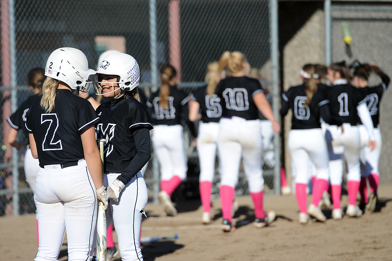 Mountain View's Kamryn Leoffler (2) talks with teammate Jaelyn Taylor after hitting a home run during their game Thursday, Oct. 4, 2018 at Mountain View High School. (Sean Star/Loveland Reporter-Herald)