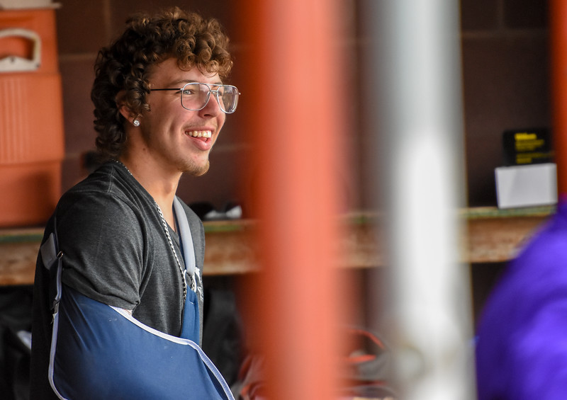 Mountain View's Nate Vondy smiles from the dugout with his arm in a sling after undergoing Tommy John's surgery before the season on Thursday April 5, 2018 at Brock Field. (Cris Tiller / Loveland Reporter-Herald)