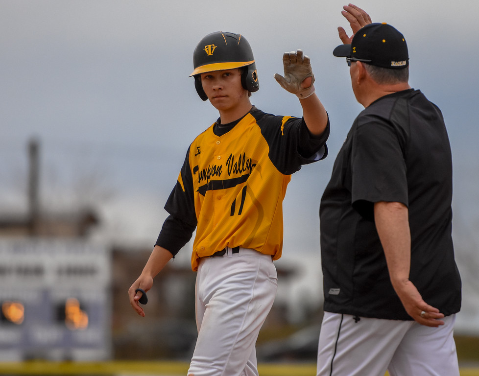 . Thompson Valley\'s Tristan Schatz receives a high five after a single against rival Mountain View on Thursday April 5, 2018 at Brock Field. (Cris Tiller / Loveland Reporter-Herald)