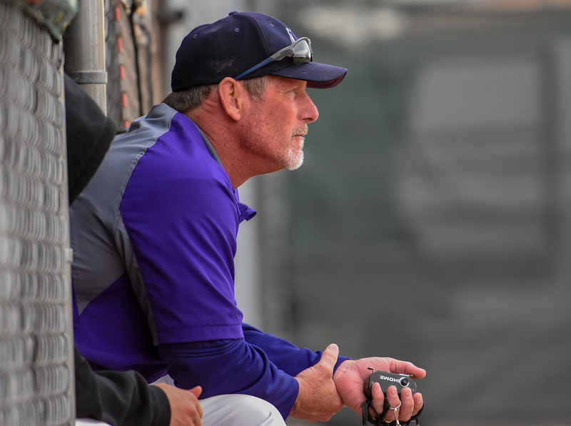 Mountain View pitching coach Brad Moore looks on from the dugout against Thompson Valley on Thursday April 5, 2018 at Brock Field. (Cris Tiller / Loveland Reporter-Herald)