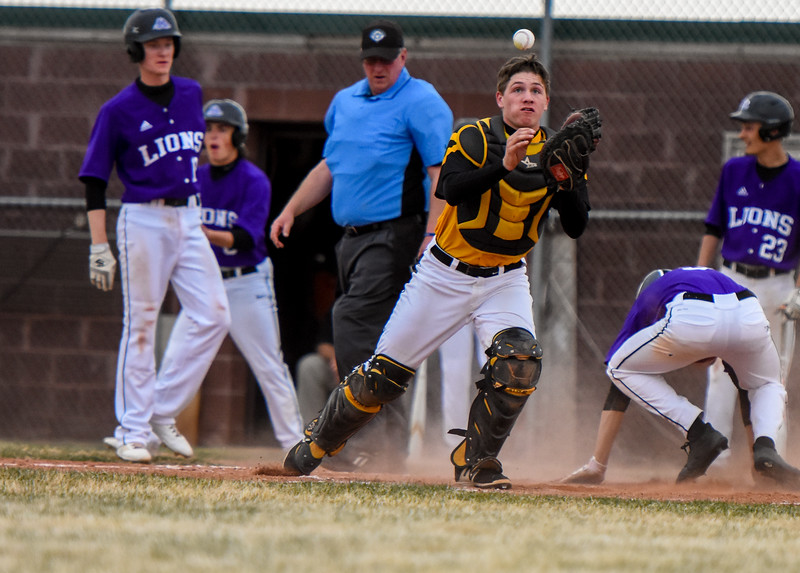 Thompson Valley catcher Trenten Riehl eyes a catch as Mountain View scores a run on Thursday April 5, 2018 at Brock Field. (Cris Tiller / Loveland Reporter-Herald)
