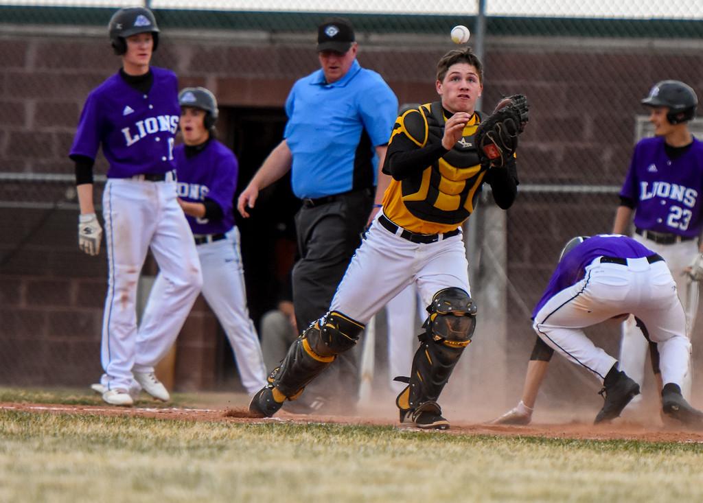. Thompson Valley catcher Trenten Riehl eyes a catch as Mountain View scores a run on Thursday April 5, 2018 at Brock Field. (Cris Tiller / Loveland Reporter-Herald)