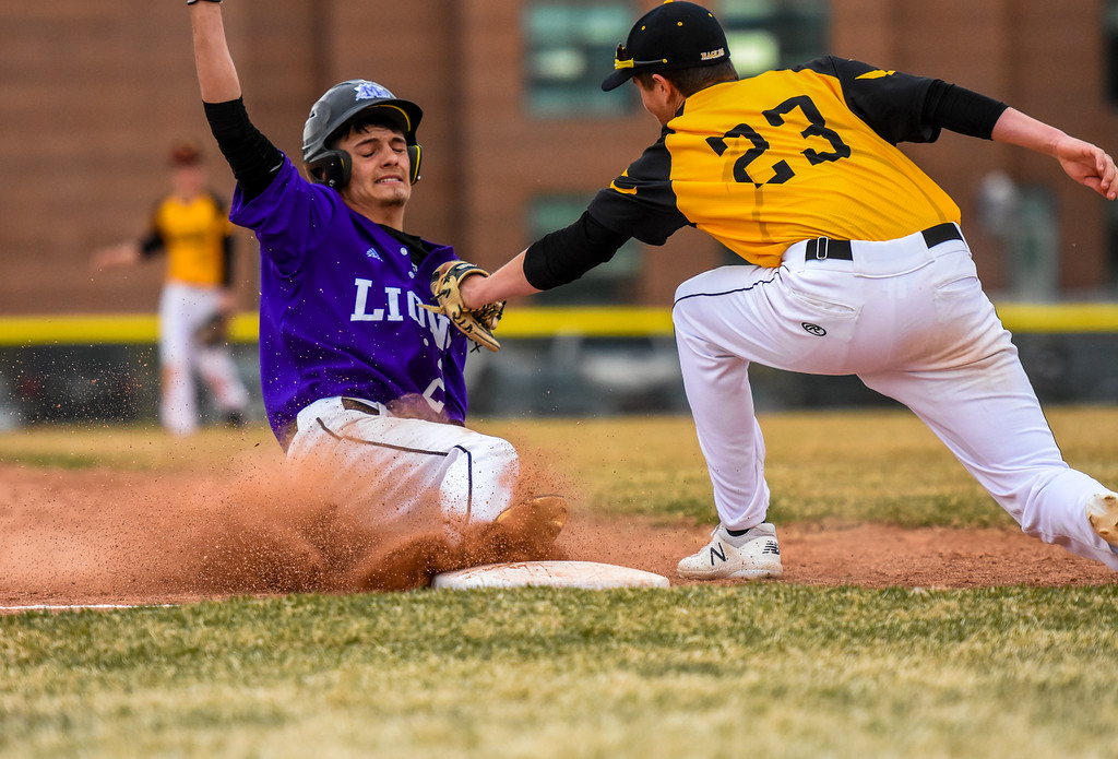 . Mountain View\'s Brexton Butcher slides into third base as Thompson Valley\'s Aidan Schultz goes for a the tag on Thursday April 5, 2018 at Brock Field. (Cris Tiller / Loveland Reporter-Herald)