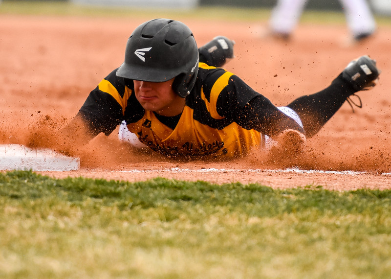 Thompson Valley's Cameron Nellor slides back into first base against rival Mountain View on Thursday April 5, 2018 at Brock Field. (Cris Tiller / Loveland Reporter-Herald)