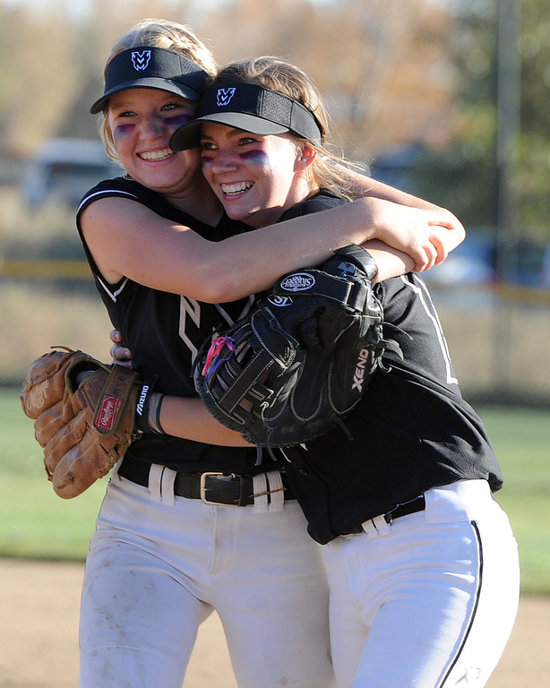 . Mountain View\'s Harley Duke, left and Michelle Pomranka hug after beating Golden during the first day of the 4A state softball tournament on Friday, Oct. 19, 2018 at Aurora Sports Park. (Sean Star/Loveland Reporter-Herald)