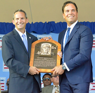 KYLE MENNIG - ONEIDA DAILY DISPATCH National Baseball Hall of Fame President Jeff Idelson, left, and Mike Piazza hold Piazza's plaque during the National Baseball Hall of Fame Induction Ceremony in Cooperstown on Sunday, July 24, 2016.