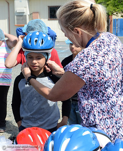 Event organizer Ann Dickman fits Andrew Strickland, 9, with a bike helmet during the Oakdale Heights School bike rodeo Friday, April 29, 2016, at the school to teach kids to ride bicycles safely in Oroville, California. Dickman said 17 bicycles were donated and children shared their bikes to get about 225 kids through the bike rodeo. (Dan Reidel -- Mercury-Register)
