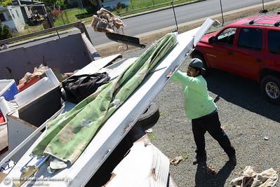 Raymond Boyer tosses trash into a 40-yard dumpster as community members clean the neighborhood Saturday, April 30, 2016, in south Oroville, California. (Dan Reidel -- Enterprise-Record)