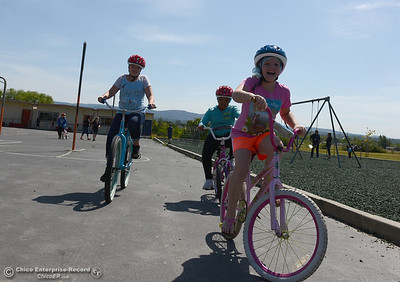 Lilly Taylor, 11, right, smiles widely as she rides with Natasha McLane, 11, left, and Roselyn Montanez, center, 10, during Oakdale Heights School's bike rodeo Friday, April 29, 2016, at the school to teach kids to ride bicycles safely in Oroville, California. Event organizer Ann Dickman said 17 bicycles were donated and children shared their bikes to get about 225 kids through the bike rodeo. (Dan Reidel -- Mercury-Register)
