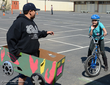 Playing the part of a car, Juan Hurtado, 11, makes eye contact with Madison Lloyd, 10, as Lloyd rides through the Oakdale Heights School bike rodeo Friday, April 29, 2016, at the school to teach kids to ride bicycles safely in Oroville, California. Event organizer Ann Dickman said 17 bicycles were donated and children shared their bikes to get about 225 kids through the bike rodeo. (Dan Reidel -- Mercury-Register)