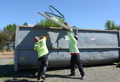 Adam Jenkins, left, and Raymond Boyer throw trash into a 40-yard dumpster as community members clean the neighborhood Saturday, April 30, 2016, in south Oroville, California. (Dan Reidel -- Enterprise-Record)