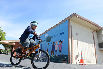 Ezekiel Vera, 11, scans with his eyes for obstacles as he rides during Oakdale Heights School's bike rodeo Friday, April 29, 2016, at the school to teach kids to ride bicycles safely in Oroville, California. Event organizer Ann Dickman said 17 bicycles were donated and children shared their bikes to get about 225 kids through the bike rodeo. (Dan Reidel -- Mercury-Register)
