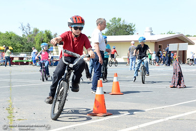 Jeremy Belloli, 10, zooms through the slalom course during Oakdale Heights School's bike rodeo Friday, April 29, 2016, at the school to teach kids to ride bicycles safely in Oroville, California. Event organizer Ann Dickman said 17 bicycles were donated and children shared their bikes to get about 225 kids through the bike rodeo. (Dan Reidel -- Mercury-Register)